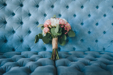 The bride's wedding bouquet of roses and peonies lies on a blue sofa in a beautiful interior. Photography, concept.