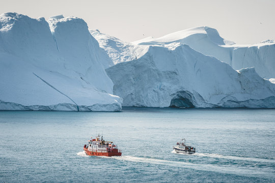 Orange whale Watching tour boat ship with icebergs in background. View towards Icefjord in Ilulissat. Greenland Disko Bay. Icebergs reflecting sunlight on a summer day.