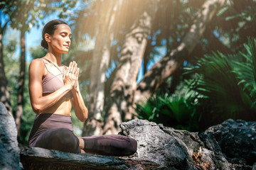 In de dag Ontspanning Listen to your soul. Full-length shot of caucasian woman sitting in Easy Seated pose, Sukhasana while practicing yoga outdoors, in a garden. Healthy lifestyle and relaxation concept