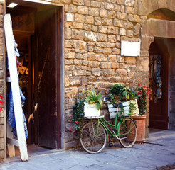Green bicycle with a lot of flowers on it on stone street in Tuscany, Italy. Italian medieval cityscape with beautiful decorated bike on it. Italian summer lifestyle. Touristic Florence.