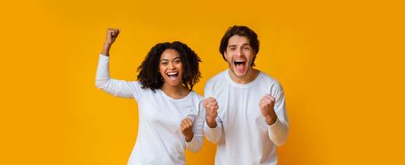 Happy interracial couple rejoicing success, celebrating victory with raised fists