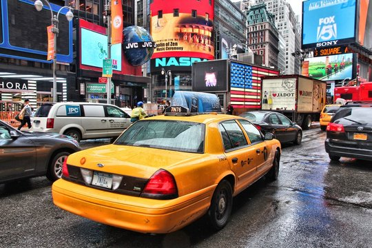 NEW YORK, USA - JUNE 10, 2013: Taxi drives in rainy Times Square, NY. Times Square is one of most recognized places in the world. More than 300,000 people pass through Times Square daily.