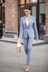 Stock photo portrait of attractive elegant brunette lady with tail in greyish blue suit with beige...