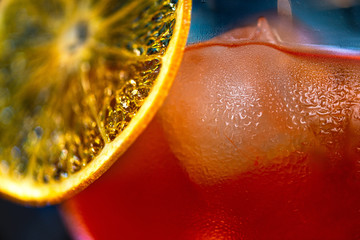 Macro abstract image of water droplets on glass of cocktail or drink with dried orange slice and ice.