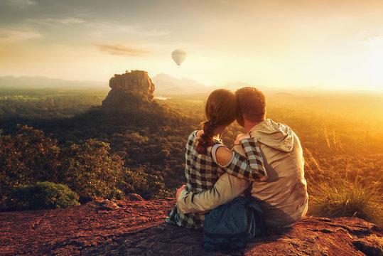 couple of travelers watch a beautiful sunset near the famous rocky plateau Lion peak, Sigiriya. Sri Lanka