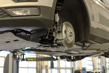 Car lifted on a lift for repair in a car service. Brake system of a modern car.