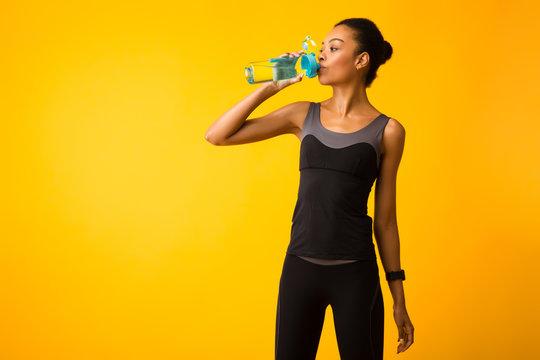 Woman In Sportswear Drinking Water Standing In Studio