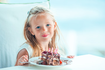 Little girl celebrate Happy Birthday with tasty cake in outdoor cafe