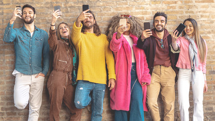 Group of multicultural friends using smartphone outdoors against a break wall - People addicted by mobile smart phone - Technology and social media concept with connected men and women