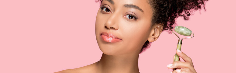 panoramic shot of attractive african american girl using jade roller, isolated on pink