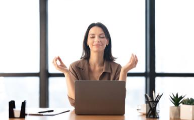 Fototapeta Girl meditating in office coping with stress obraz