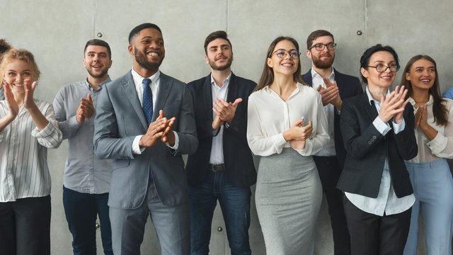 Diverse business colleagues clapping hands after meeting