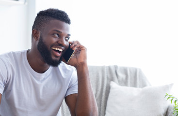 Talkative african american man talking on phone with friends