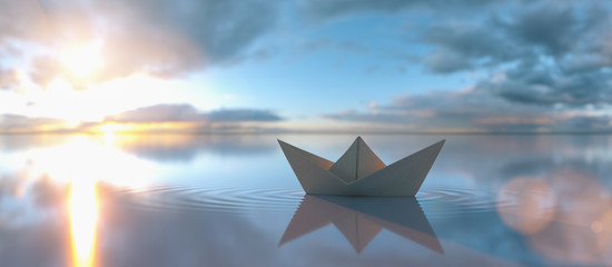 Paper boat in a calm water at sunrise sunset with cloudy sky, copyspace for your individual text.