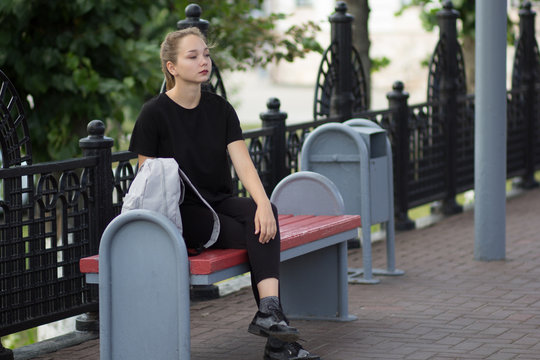Young woman with thinking look sitting on the bench with bag and looking aside