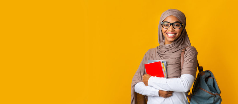 Portrait of black girl student in headscarf with backpack and notepads