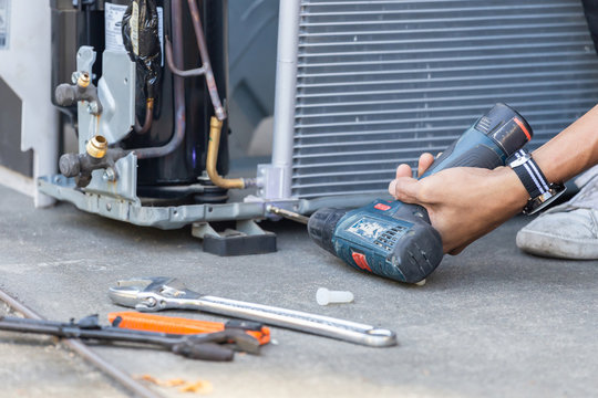 Selective focus Air Conditioning Repair, technician man hands using a screwdriver fixing modern air conditioning system