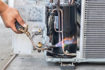Close up of Air Conditioning Repair use fuel gases and oxygen to weld or cut metals, Oxy-fuel welding and oxy-fuel cutting processes, repairman on the floor fixing air conditioning system Fotobehang
