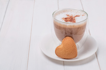 Fotobehang - Cup of coffee and sweet heart shaped bisquit on white table