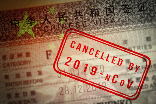 Coronavirus COVID-19 2019-nCoV epidemic. China closing borders and restricted access. Chinese visa closeup with stamp mark Cancelled by 2019-nCoV and overlaid by flag