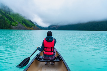 Canvas Prints Pool Woman paddling a canoe through Lake Louise