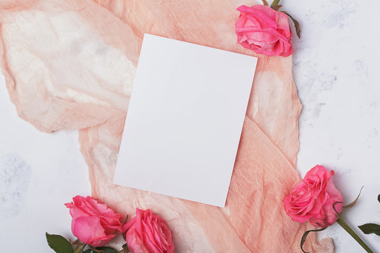 Top view of blank paper card lying on the gentle light pastel color cloth on the table with pink roses.