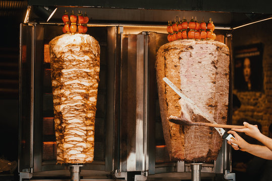 Chef cutting with doner knife Traditional Turkish Doner Kebab meat.