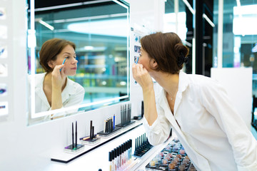 young attractive girl in a white shirt paints eyelids with a pencil looking at the mirror in a professional cosmetics store