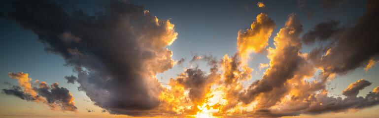 Fotobehang - Shining sun and dark clouds at sunset