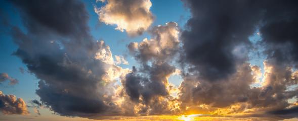 Fotobehang - Dark clouds and shining sun at sunset