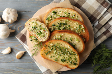 Plate with toasted garlic bread and dill on wooden background, top view