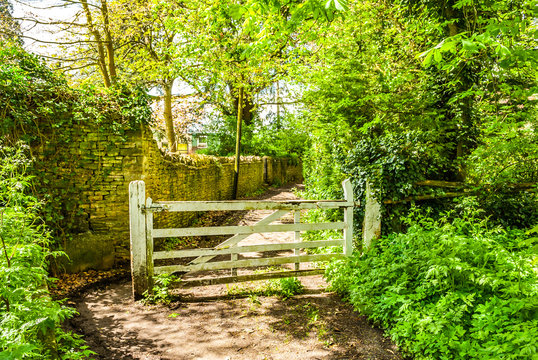 Footpath next to a wall with large white five bar gate. Chipping Norton