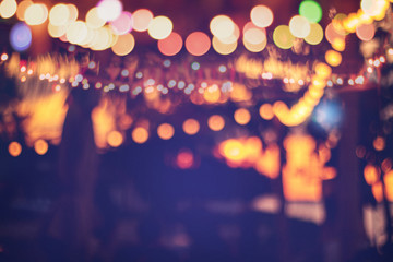 blurred bokeh light on sunset with yellow string lights decor in beach resort