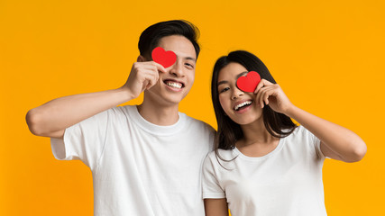 Happy asian couple covering one eye with valentine cards Fotomurales
