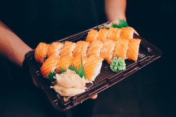 Foto op Plexiglas Sushi bar Close-up Hand Waiter holding Set Delicious fresh Sushi slate plate, Japanese raw fish in traditional restaurant. Philadelphia flesh Rolls served on plate in sushi bar. Copy Space Japan menu service