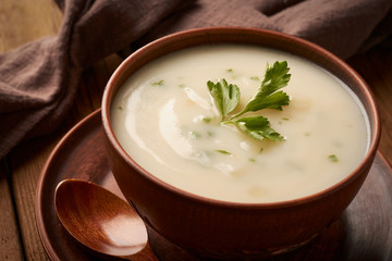 Bowl of potato soup with parsley on a wooden background