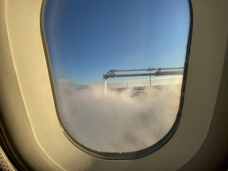Passenger view of de-icing airplane at the airport