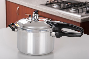 Double valve pressure cooker on white background.