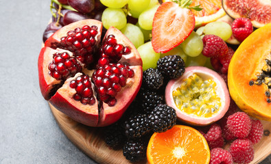 Wall Mural - Delicious fruit platter pomegranate papaya oranges passion fruits berries on wooden board on light concrete background, selective focus, copy space
