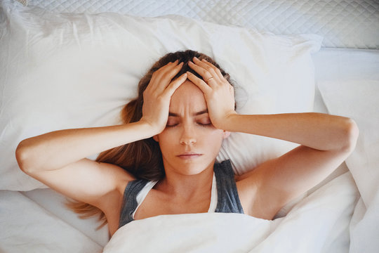 Beauty, young woman with headache on bed