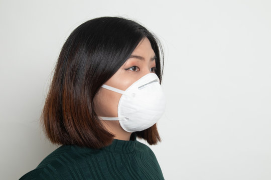 Young Asian woman wearing N95  mask to prevent PM2.5 dust air pollution