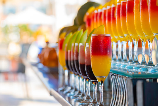 Row of glasses with natural juice on the bar near the pool. Summer luxury tropical restaurant. Elegant cocktails set with fruits.
