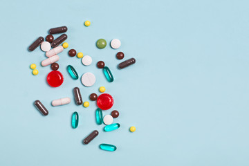 Different multi colored pills and tablets on blue background.