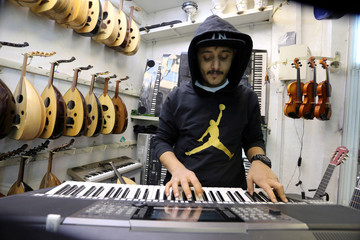 A Saudi youth plays organ at the musical instruments shop at the Hilla market, in Riyadh