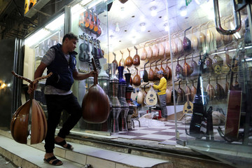 Workers are seen at the musical instruments shop at the Hilla market, in Riyadh