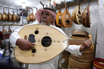 A Saudi musician plays at the oud instrument in a musical instruments shop at the Hilla market, in Riyadh