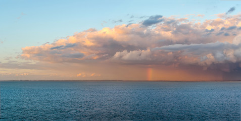 Panoramic image of a heavy rain storm and clouds over the coast of Denmark with a rainbow emerging over the Baltic Sea in Northern Europe.