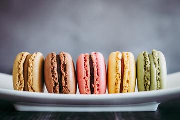 Poster Macarons Assortiment de macarons colorés sur une assiette blanche