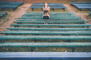Depressed lonely girl siiting on bench in park and covering her crying face with hands. Despair and loneliness concept.
