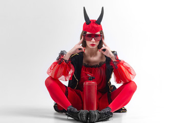 Portrait of passionate sexy babe in red stockings and devil horns sitting with fire extinguisher between her legs over white background